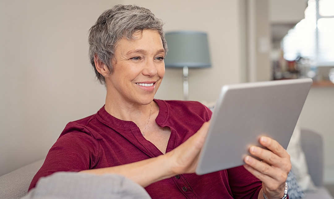 Image of a woman at home sitting on the sofa using an iPad and smiling.