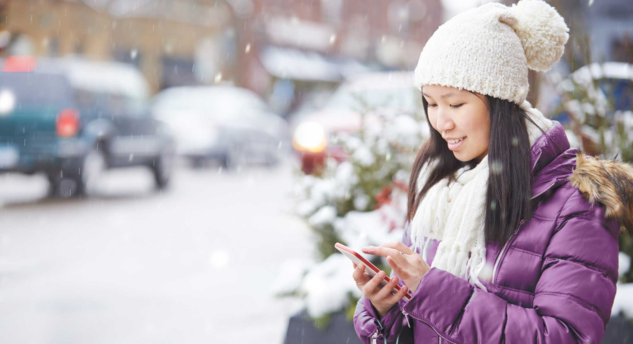 Image of a woman using her NatWest app in the snow.