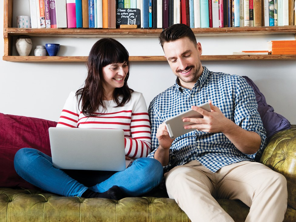 Woman and man on sofa browsing on mobile devices